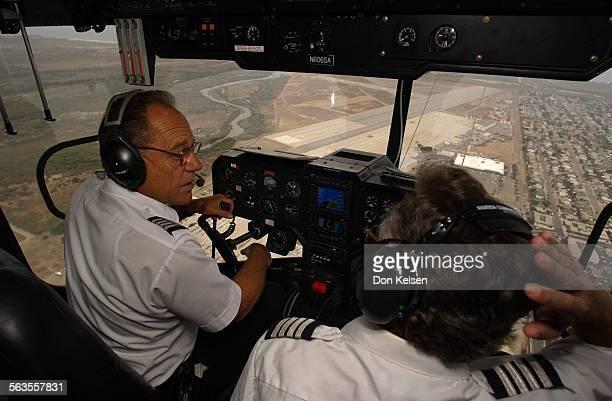 – Pilot Corky Belanger and co–pilot Dick Esh maneuver blimp over Imperial Beach Naval Auxiliary Landing Field Tijuana River seen left of the landing...
