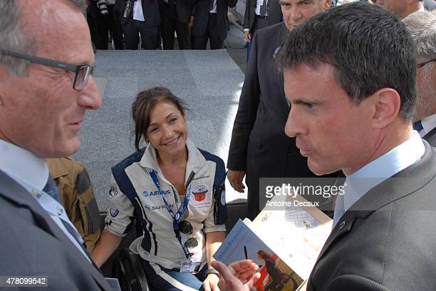 Pilot Dorine Bourneton gives her last book Au Dessus Des Nuages to the France Prime Minister Manuel Walls before taking part in the first worldwide...