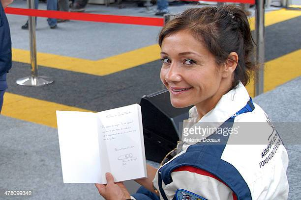 Pilot Dorine Bourneton shows the dedication she wrote on her last book 'Au Dessus Des Nuages' to the France Prime Minister Manuel Walls before taking...