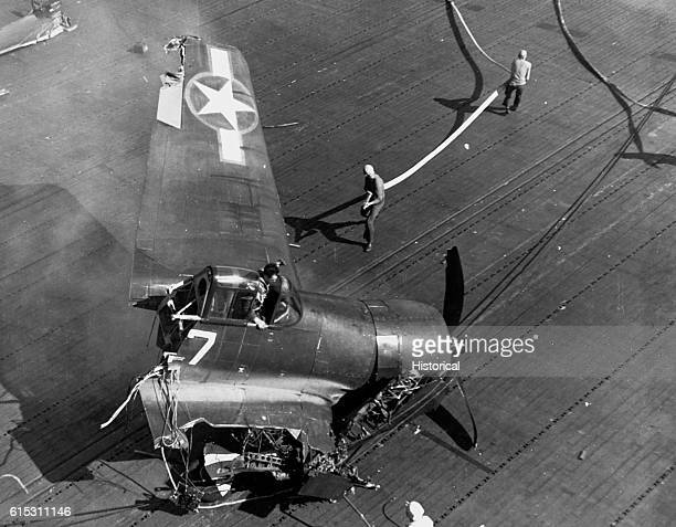 Pilot Ensign R Black climbs out of an F6F fighter aircraft following a crash landing onto the USS Yorktown Crew members bring a fire hose to combat...
