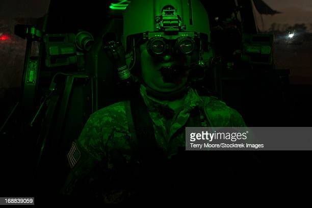 a pilot equipped with night vision goggles in the cockpit of an ah-64 apache helicopter. - apache helicopter stock pictures, royalty-free photos & images