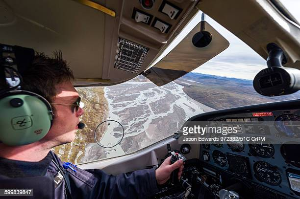 A pilot flying a light plane over an outwash plain created by a river flowing with meltwater and sediment from a glacier Qinnguata Kuussua River...