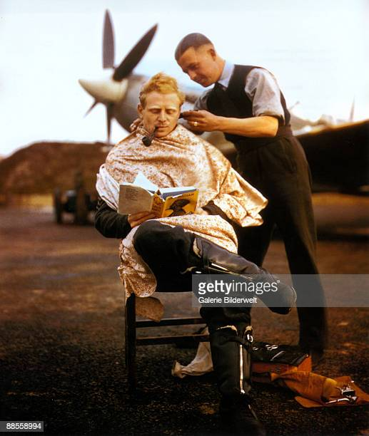RAF pilot Flying Officer Francis Mellersh gets a haircut between missions while reading John Buchan's 'Greenmantle' Fairlop airfield Essex November...