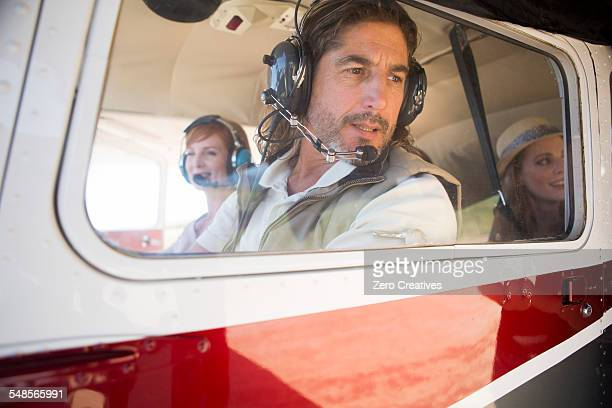 Pilot flying tourists in airplane
