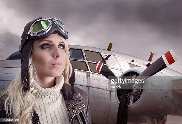 pilot girl with retro equipment and airplane behind - aviator's cap stock pictures, royalty-free photos & images