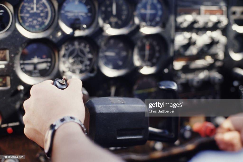 Pilot handling controls, close-up (focus on hand) : Stock Photo