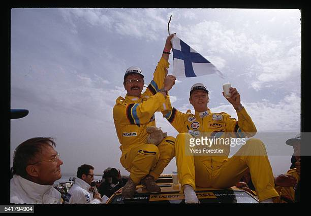 Pilot Hari Vatanen and his copilot celebrate their victory in the car category of the 1990 Paris Dakar Rally by waving a Finnish flag
