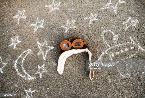 pilot hat and flying goggles lying on asphalt painted with airplane, moon and stars - aviation hat stock photos and pictures