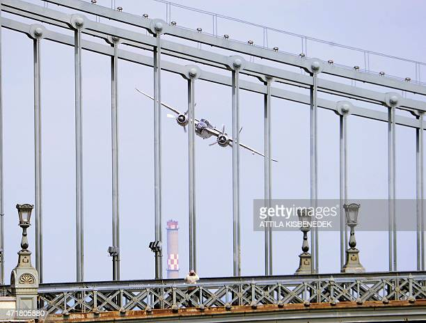 A pilot in a A B25 type airplane performs over the oldest Hungarian bridge the 'Lanchid' on May 1 2015 during a flying and car show around the Danube...