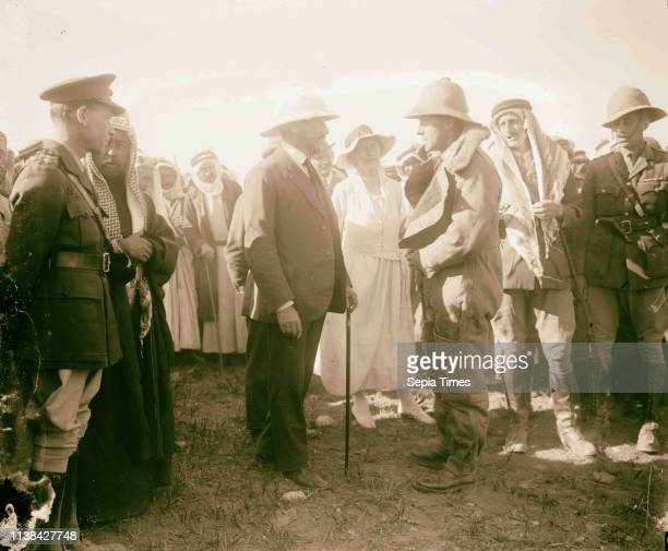 Pilot in flight suit greets Sir Herbert Samuel Gertrude Bell stands between Samuel and pilot Wyndham Deedes and Amir Abdullah to the left in...