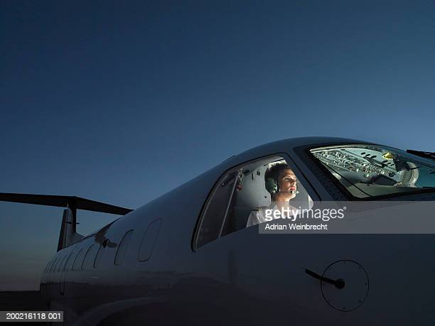 pilot in illuminated cockpit of plane wearing headphone, looking ahead - piloting stock pictures, royalty-free photos & images
