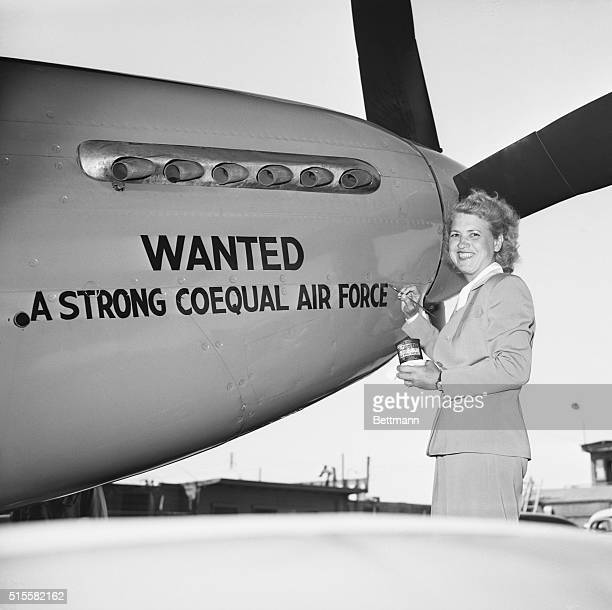 Pilot Jacqueline Cochran paints a message on her airplane She hopes it will help the Army Air Forces Aid Society
