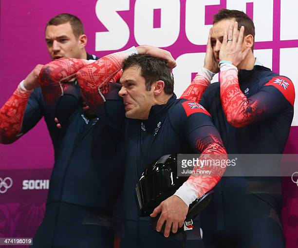 Pilot John James Jackson Stuart Benson and Bruce Tasker of Great Britain team 1 react after the news of the crash of Canada team 3 during the Men's...