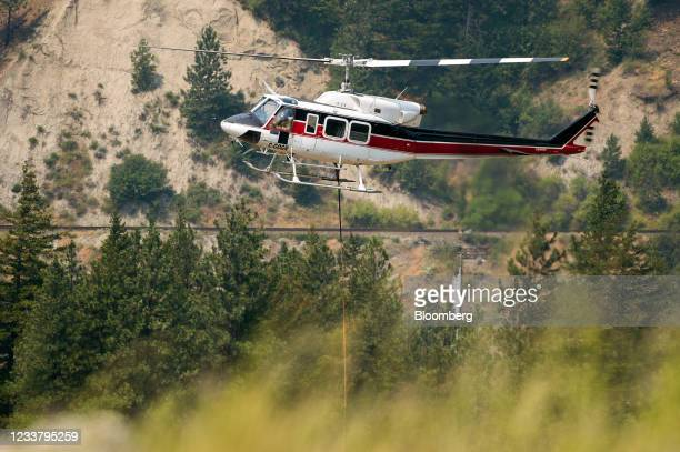 Pilot maneuvers a helicopter water bomber into a staging area south of the Lytton Wildfire in the town of Lytton, British Columbia, Canada, on...
