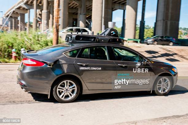 A pilot model of an Uber selfdriving car drives down a street on September 13 2016 in Pittsburgh Pennsylvania Uber launched a groundbreaking...
