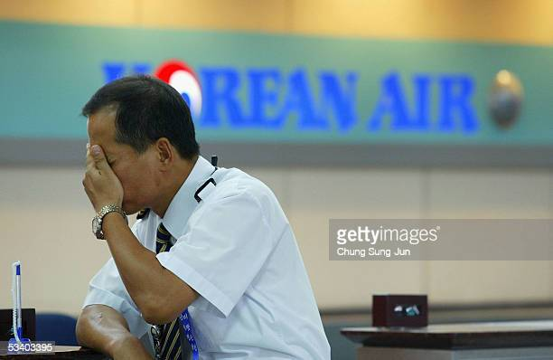 Pilot of Korean Air stands at the Korean Air's ticket and checkin desk at Gimpo Airport on August 18 2005 in Seoul South Korea South Korea's largest...