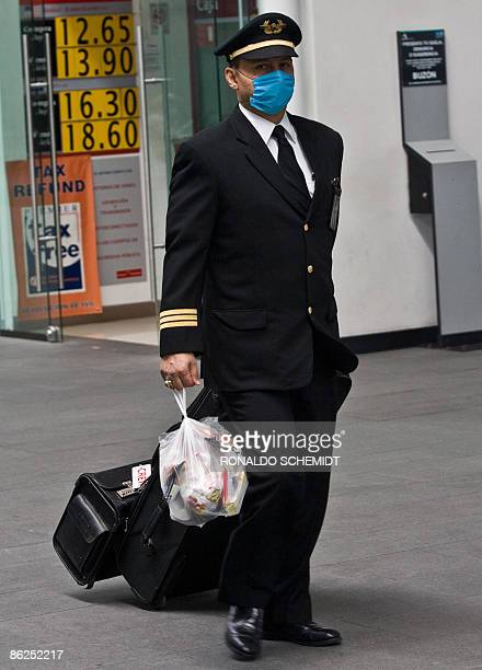A pilot of the Mexican airline Aeromexico walking at Mexico City's international airport on April 27 2009 wears a surgical mask to ward off contagion...