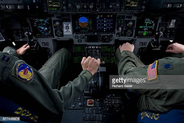 Pilot of the US Air Force holds the throttle levers in the cockpit of a C-17 transport jet at the Farnborough Air Show, UK. The Boeing C-17...