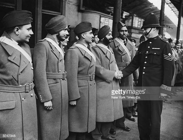A policeman shakes hands with a group of Indian pilots who had come to Great Britain to join the Royal Air Force during World War II London England