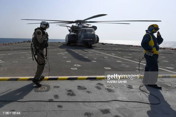 A US pilot on Britain's RFA Cardigan Bay landing ship prepares to board a Black Hawk helicopter for a reconnaissance flight in the Gulf waters off...