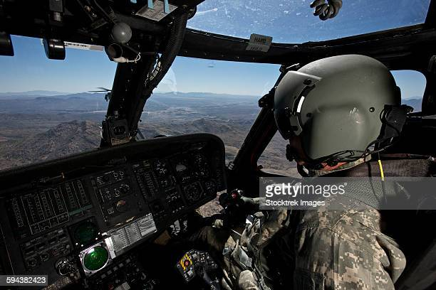 Pilot operating the cockpit of a UH-60 Black Hawk helicopter.