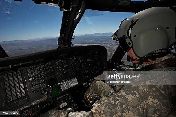 pilot operating the cockpit of a uh-60 black hawk helicopter. - inside helicopter stock pictures, royalty-free photos & images