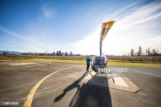 pilot prepares his helicopter prior to a flight. - helicopter photos stock pictures, royalty-free photos & images
