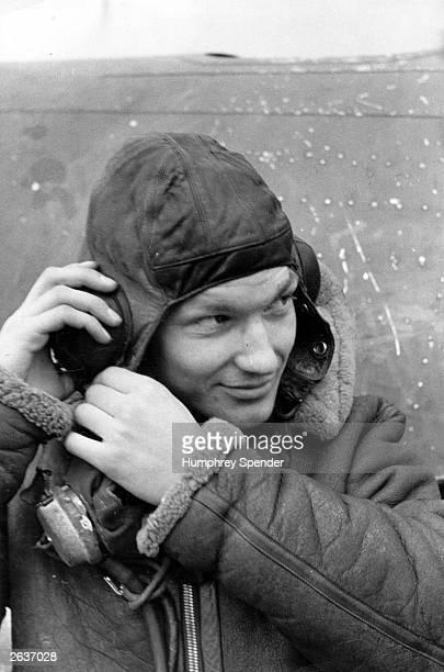 A RAF pilot puts on his headgear Original Publication Picture Post 275 A Day With A Flight Squadron pub 1940