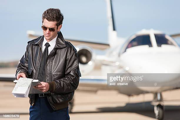 pilot reviewing flight map outside corporate jet - bomber jacket stock pictures, royalty-free photos & images