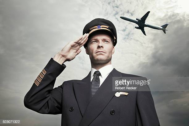 pilot saluting with airplane overhead - saluting stock pictures, royalty-free photos & images