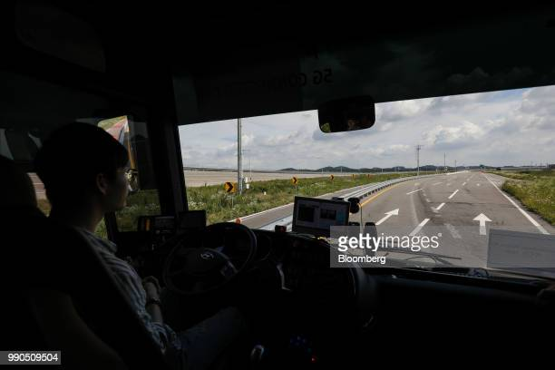 A pilot sits inside an autonomous 5G connected bus operated by KT Corp during a test drive at KCity in Hwaseong South Korea on Tuesday July 3 2018...