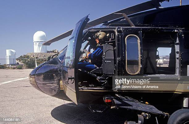 A pilot sitting in the cockpit of the Night Hawk helicopter used by the US Customs Department at a Kitt Peak Arizona heliport