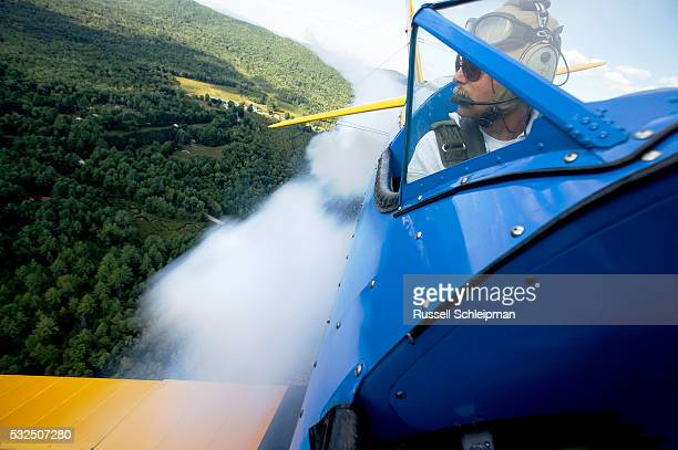 pilot skywriting in vintage biplane - acrobatic activity stock pictures, royalty-free photos & images
