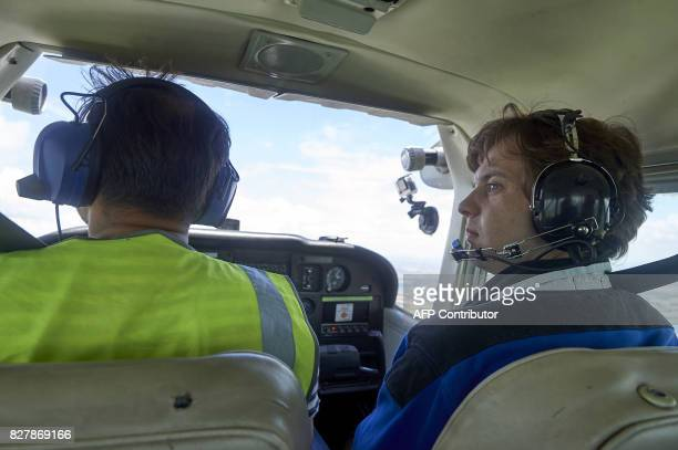 Pilot Somasekhara Pemmireddy and passenger Adam Nicholas sit in the cockpit during a flight over the capital in a Cessna 172 plane at the London...