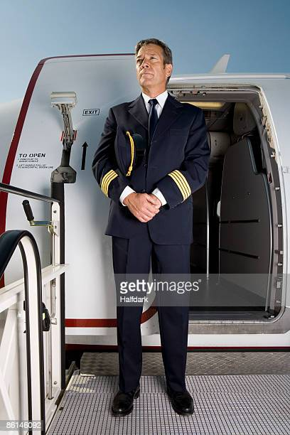 a pilot standing in front of the doorway of a plane - aviation hat stock photos and pictures