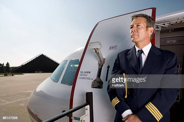 A pilot standing in front of the doorway of a plane
