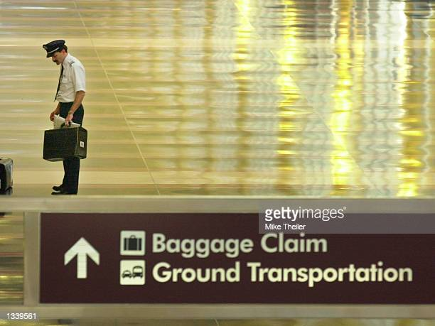 A pilot stands alone with his chart case on the empty concourse of Ronald Reagan National Airport September 18 2001 in Virginia Reagan National...