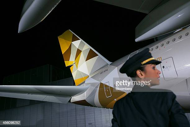 A pilot stands in front of Etihad Airways PJSC's first Airbus A380 aircraft during its unveiling at Airbus Group NV's paint plant in Hamburg Germany...
