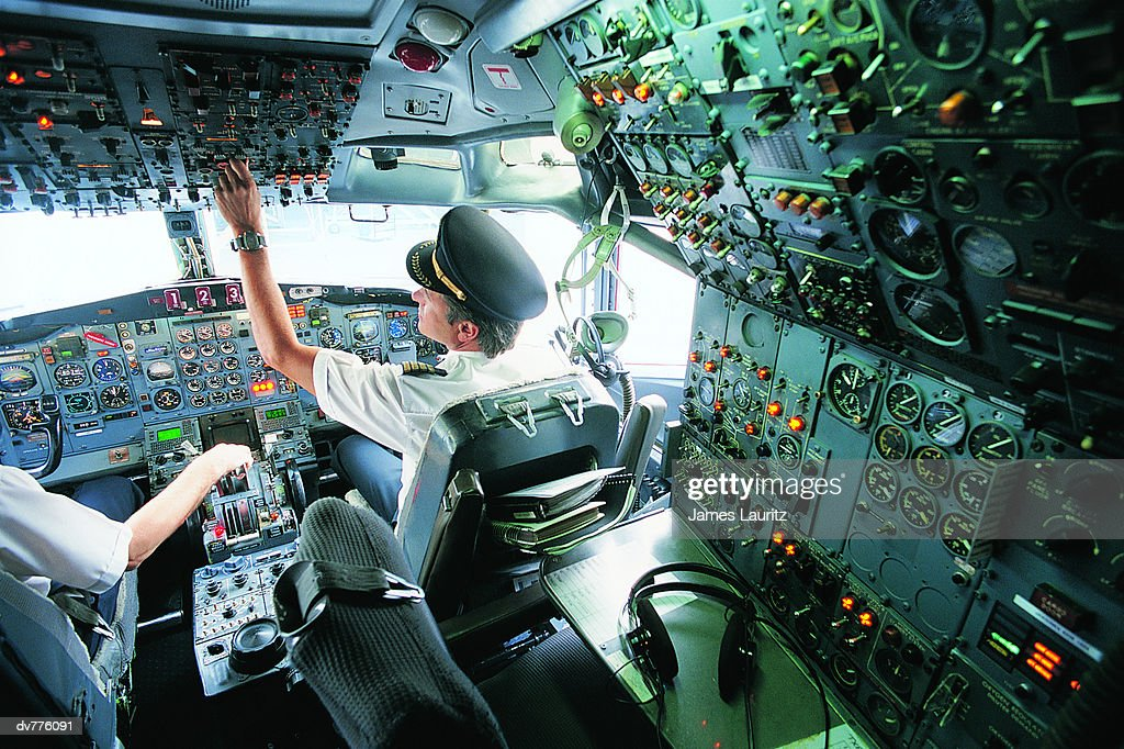 Pilot Switching a Control in the Cockpit of a Commercial Aeroplane : Stock Photo