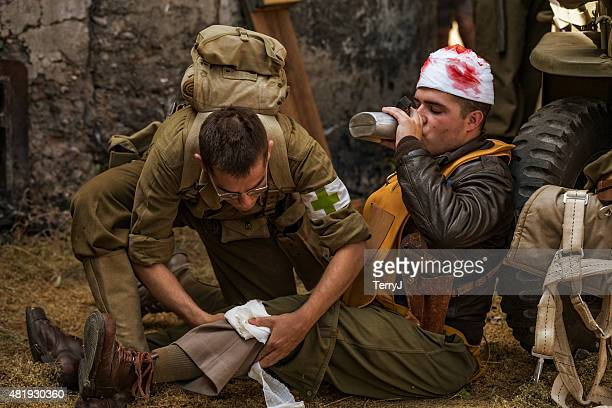 wwii pilot takes drink of water while medic attends wounds - attending stock pictures, royalty-free photos & images