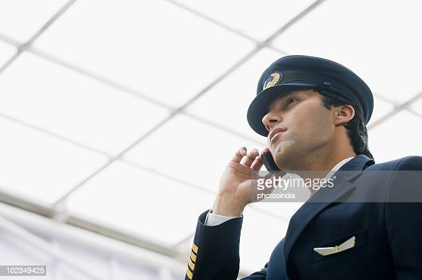 pilot talking on a mobile phone at an airport - uniform cap stock pictures, royalty-free photos & images
