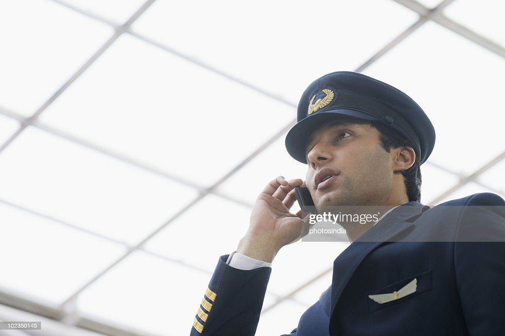 Pilot talking on a mobile phone at an airport : Stock Photo