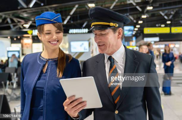 Pilot talking to a flight attendant and showing her something on a tablet computer