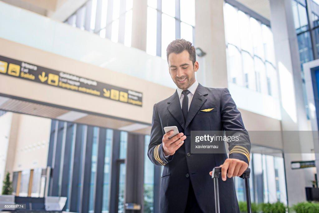 Pilot using smart phone in airport : Stock Photo