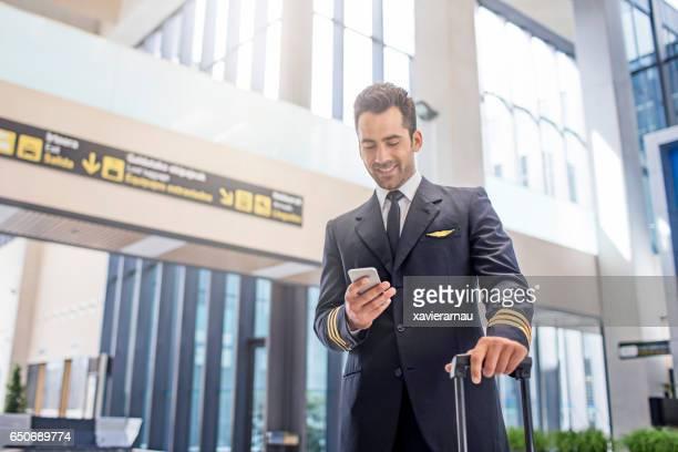 Pilot using smart phone in airport