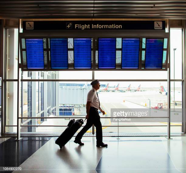 pilot walking through o'hare airport terminal - ohare airport stock pictures, royalty-free photos & images
