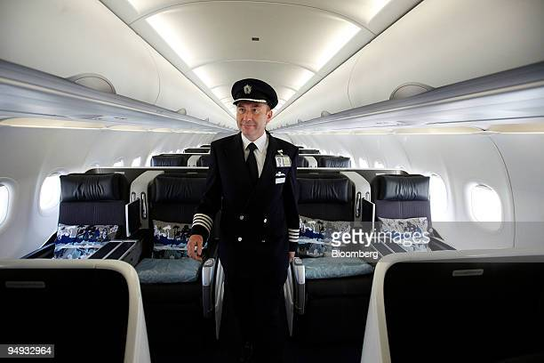 A pilot walks through the cabin of a British Airways businessclass only service airplane at London City Airport in London UK on Tuesday Sept 29 2009...