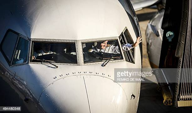 A pilot waves as a Ryanair plane arrives at Schiphol Airport in Amsterdam The Netherlands on October 27 2015 Irish lowcost airline Ryanair starts a...