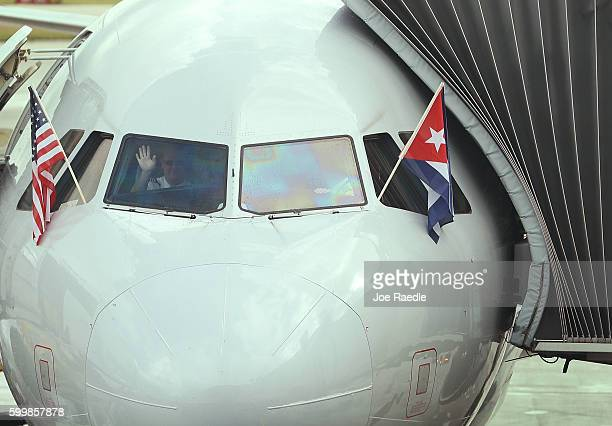 Pilot waves as he prepares to push back from the gate in American Airlines Flight 903, becoming the first commercial flight from Miami to Cuba in...