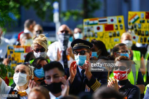 A pilot wearing a protective face mask applauds during a protest by Deutsche Lufthansa AG employees and union members outside the Lufthansa Aviation...